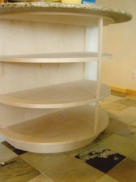 Bottom shelves in half-moon shaped custom shelving in remodel of kitchen room in Denver
