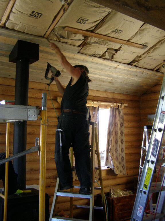 Randy working on custom wood ceiling in remodel of cabin room in Wyoming