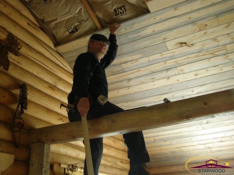 Randy installing custom wood ceiling in remodel of cabin room in Wyoming