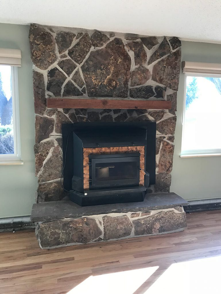Stone fireplace before remodel of living room in Golden