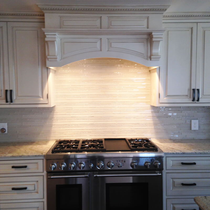A gas stove with traditionally styled hood in remodel of kitchen in Denver