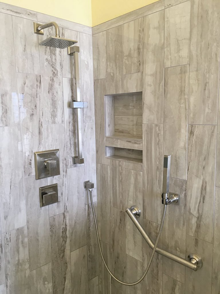 Interior view of shower with modern fixtures in remodel of bathroom in Lakewood