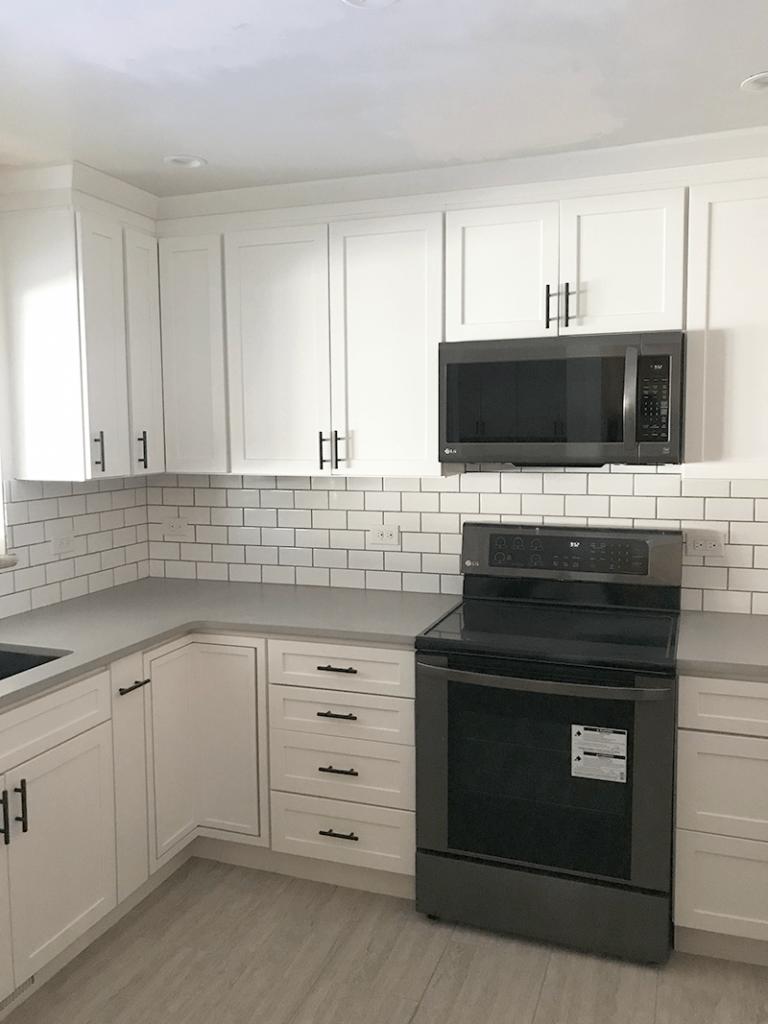 White cabinets with tile backsplash in remodel of kitchen in North Denver
