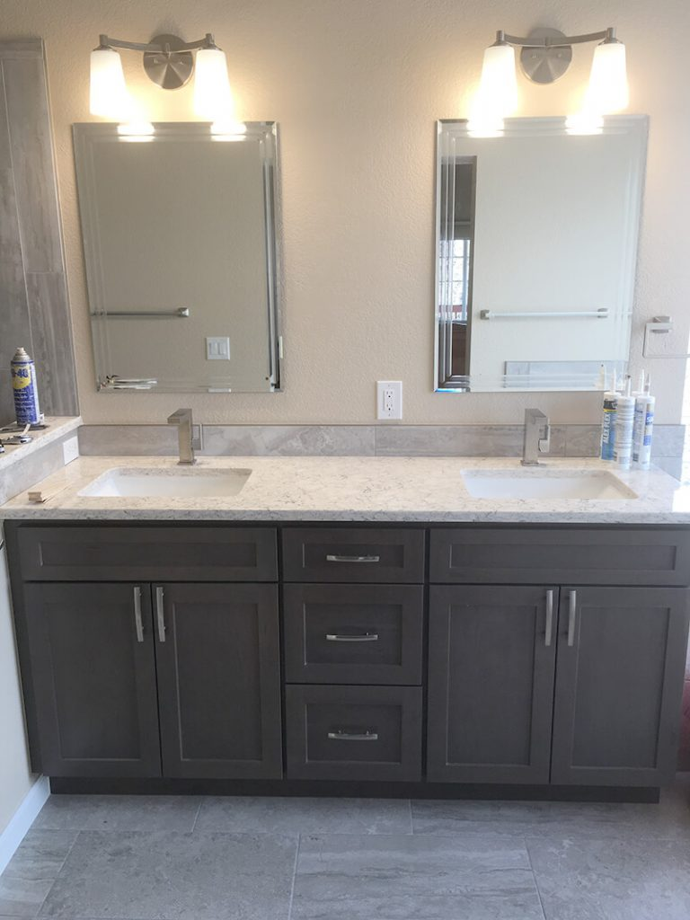 A dual sink vanity with new mirrors and lighting fixtures in remodel of bathroom in Lakewood
